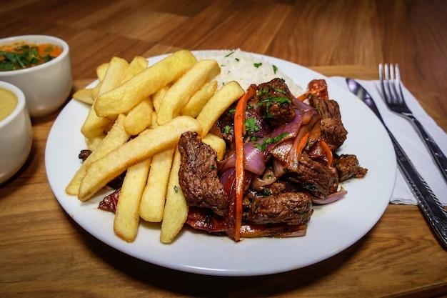 Peruanisches essen lomo saltado, pommes frites mit fleisch, zwiebeln, gelbem pfeffer, petersilie, weißem reis und sojasauce, auf einem weißen teller mit besteck und holzhintergrund.