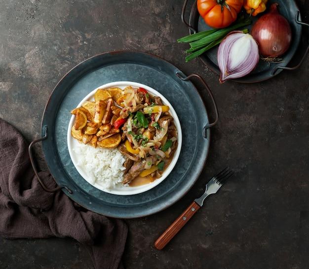 Peruanisches gericht lomo saltado aus rinderfilet mit roten zwiebeln, gelbem chili, tomaten, kartoffelpommes und reis.