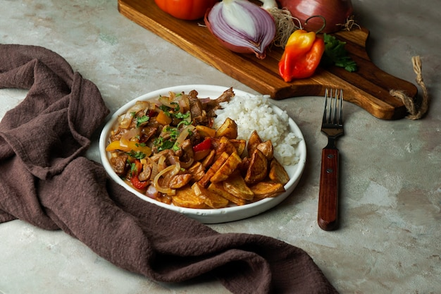 Peruanisches gericht lomo saltado, hergestellt aus rinderfilet mit roter zwiebel, gelbem chili, tomaten, mit kartoffelpommes und reis