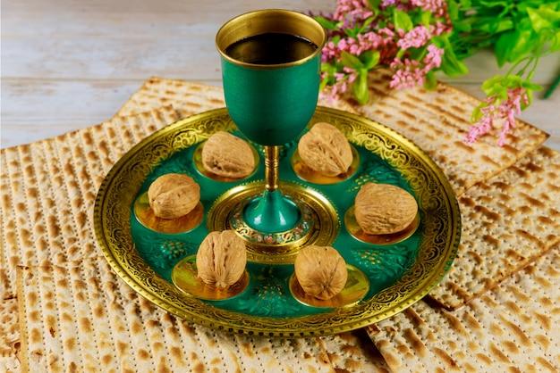 Pessach-konzept. jüdische matze, kiddusch und seder mit text in hebräischem ei, knochen, kräutern, karpas, chazeret und charoset.