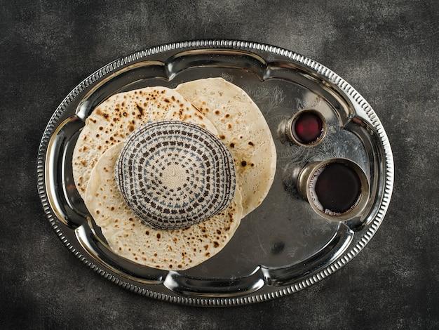 Pessach matzoh jüdisches feiertagsbrot, zwei gläser koscherer wein und kippah über steintisch.