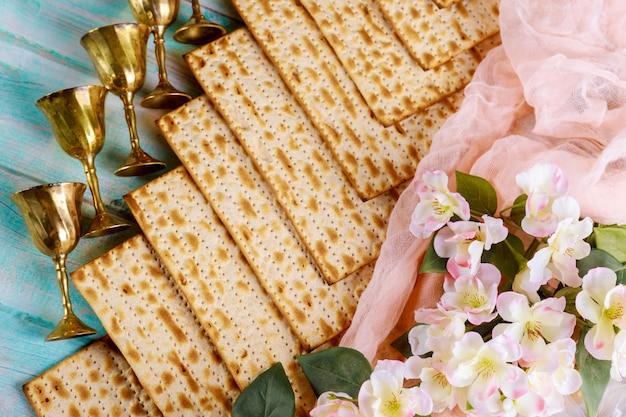 Pessachmatzah mit blühendem zweig und weinbechern.