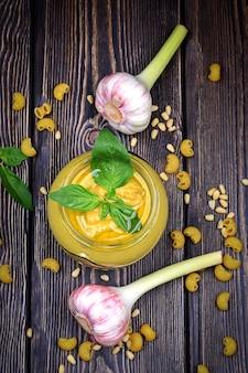 Pesto-sauce für pasta auf dunklem holzhintergrund. zedernnüsse, basilikum, knoblauch, olivenöl, käse