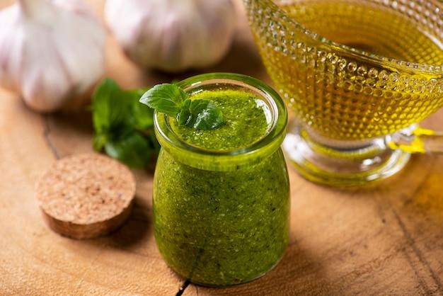 Pesto-sauce. in einem transparenten glas mit den zutaten im hintergrund. olivenöl, knoblauch und basilikum.
