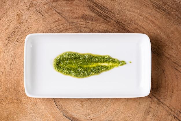 Pesto-sauce. in einem transparenten glas mit den zutaten in der oberfläche. olivenöl, knoblauch und basilikum.