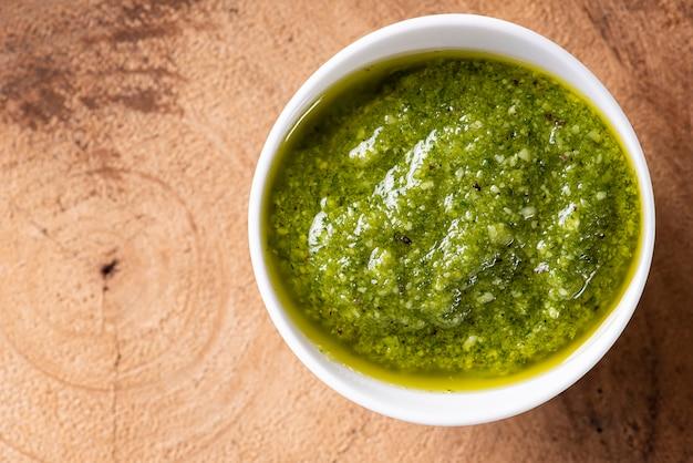 Pesto-sauce in einer schüssel auf einem holztisch