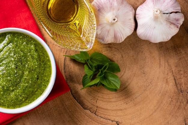 Pesto-sauce in einer schüssel mit den zutaten im hintergrund. olivenöl, knoblauch und basilikum.