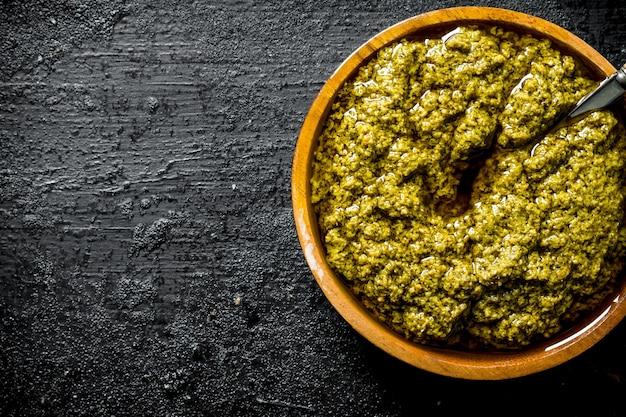 Pesto-sauce in holzschale mit löffel. auf schwarz rustikal