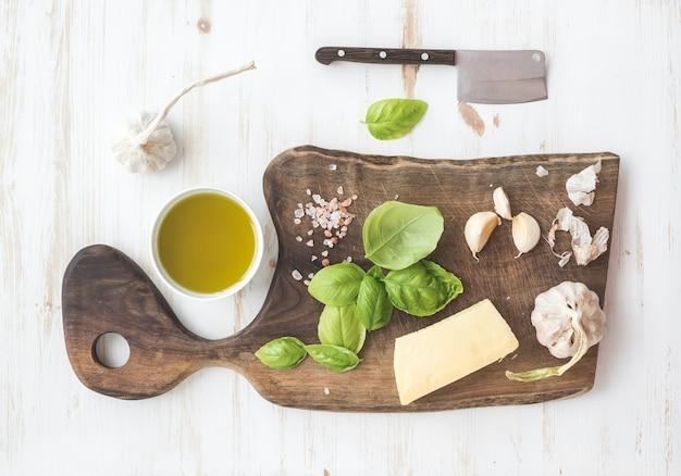 Pesto sauce kochset. frischer basilikum, olivenöl, parmesankäseparmesankäse und knoblauch auf hackendem brett der rustikalen walnuss über weißem holztisch