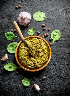 Pesto-sauce mit basilikum, knoblauch und pinienkernen. auf schwarz rustikal