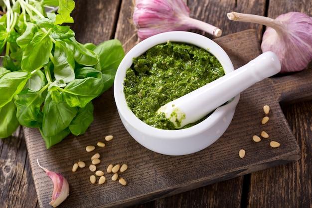 Pesto-sauce mit frischem grünem basilikum und knoblauch auf holzbrett
