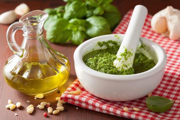 Pesto-soße und zutaten über rustikalem holzhintergrund