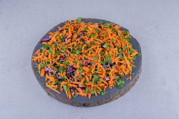 Petersilie, karotte und rotkohl gehackt in einen salat auf einem brett auf marmorhintergrund.