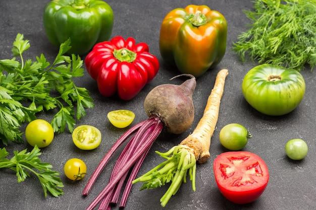 Petersilienwurzel, rüben und tomaten. dill- und petersilienzweige. schwarzer hintergrund. ansicht von oben