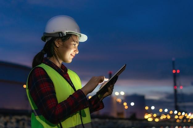 Petrochemie-ingenieurin, die mit digitalem tablet arbeitet