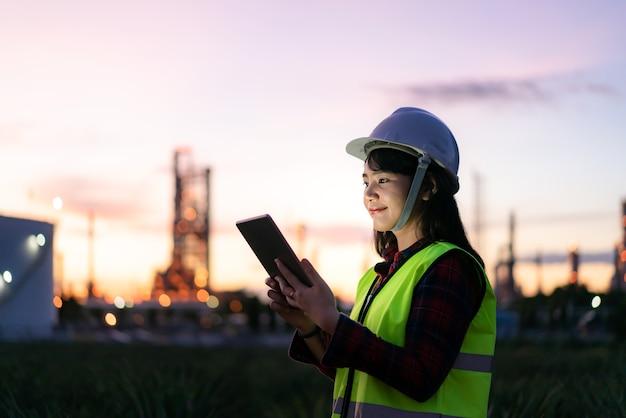 Petrochemie-ingenieurin, die nachts mit digitalem tablet arbeitet.