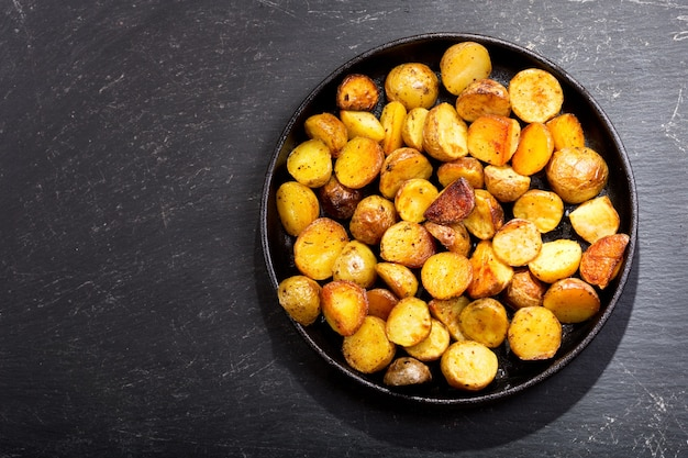 Pfanne bratkartoffeln auf dunklem tisch