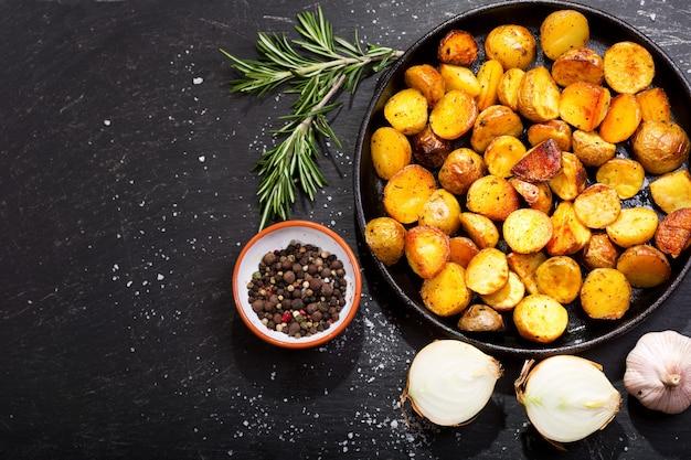 Pfanne bratkartoffeln mit rosmarin auf dunklem tisch