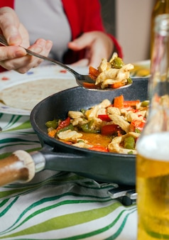 Pfanne mit mexikanischen fajitas auf einem tisch mit einer person, die essen serviert