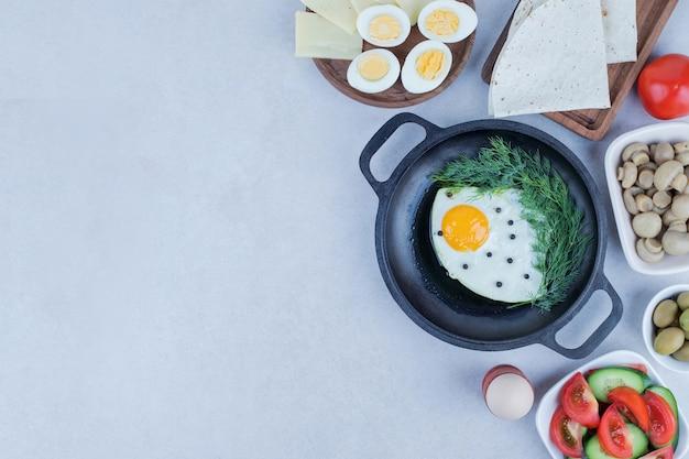 Pfanne mit omelett und gekochten eiern, käse, tomaten, pilzen.