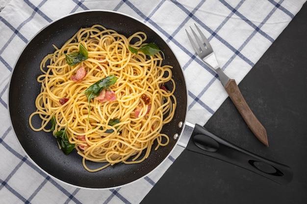 Pfanne mit spaghetti-nudeln mit getrocknetem chili, knoblauch, süßem basilikum und speck neben gabel und serviette auf dunklem texturhintergrund, draufsicht