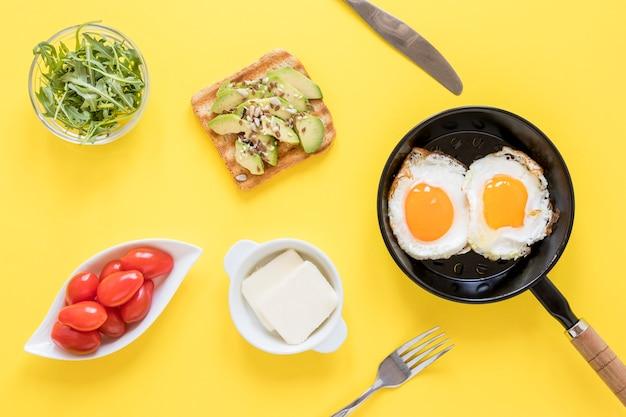 Pfanne mit spiegeleiern und toast zum frühstück auf dem tisch