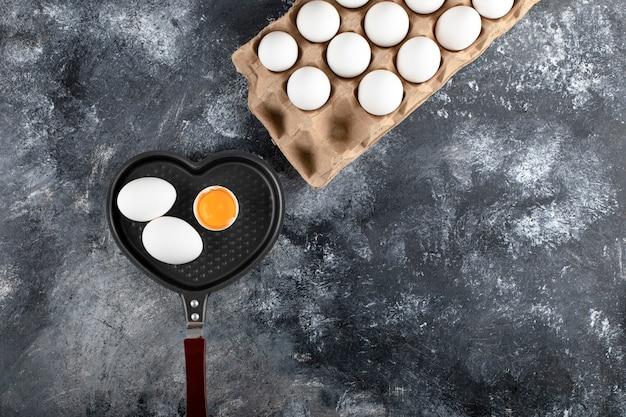 Pfanne und behälter mit eiern auf marmoroberfläche.