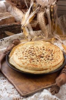 Pfannkuchen auf einem teller. der rustikale tisch ist mit einer gestrickten weißen tischdecke bedeckt. helle farbpalette. kindheitserinnerungen