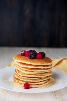 Pfannkuchen auf einem weißen teller mit früchten auf holzuntergrund
