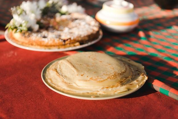 Pfannkuchen auf einer roten tischdecke. maslenitsa. winter tea party.