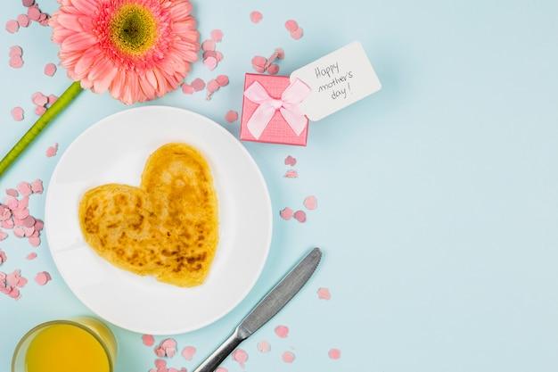 Pfannkuchen auf platte in der nähe von blumen, glas und geschenk mit tag