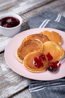 Pfannkuchen auf teller zum frühstück mit marmelade und löffel