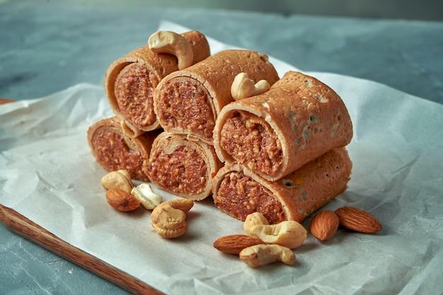 Pfannkuchen (crepes) gefüllt mit geriebenen datteln und nüssen auf einem grau