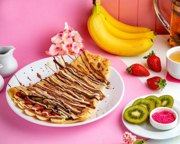 Pfannkuchen-crepes mit schokoladen-bananen-erdbeere und kiwi auf dem tisch