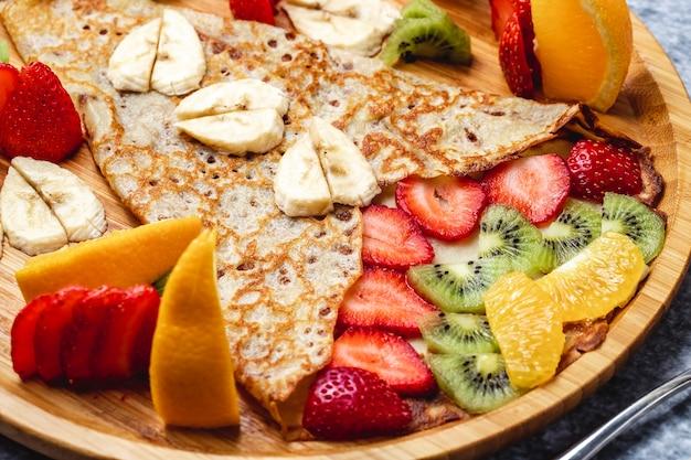 Pfannkuchen-crepes von der seite mit bananen-erdbeer-kiwi und orange auf einem teller