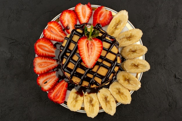 Pfannkuchen der draufsicht köstlich mit früchten und schokolade auf dem dunklen hintergrund