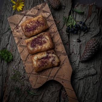 Pfannkuchen der draufsicht mit hausgemachtem fleisch auf holzständer auf baumrinde