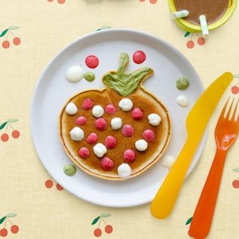 Pfannkuchen-frühstücksleckerbissen für kinder in form einer lustigen erdbeere