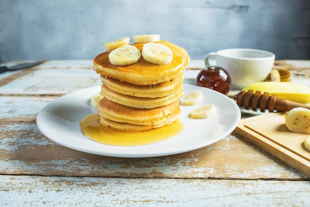 Pfannkuchen garniert mit honig und bananen auf dem tisch
