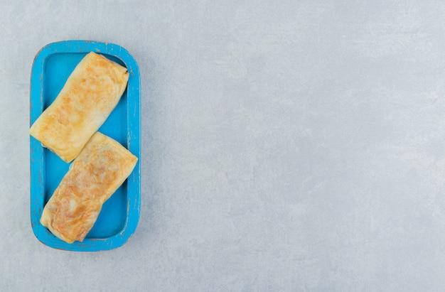Pfannkuchen gefüllt mit fleisch auf blauem teller.