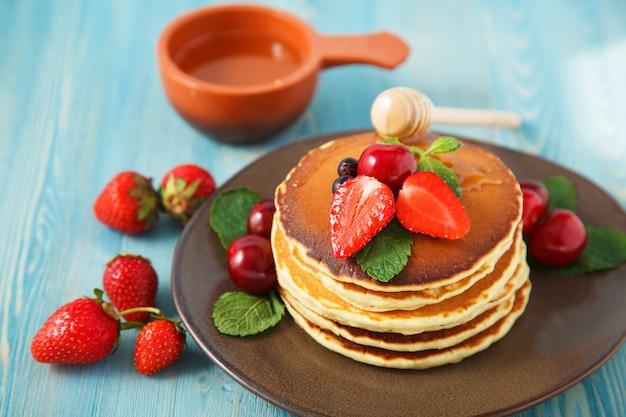 Pfannkuchen in einer platte mit erdbeeren, minze, honig und kirsche auf einem hellen blauen hintergrund.