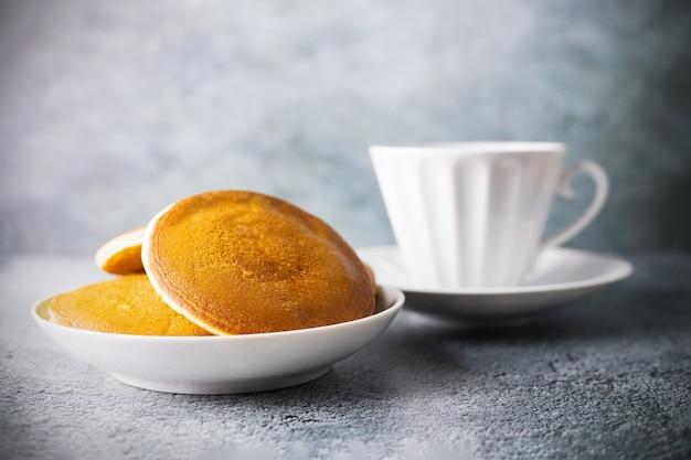 Pfannkuchen in schale und verschwommene porzellantasse tee oder kaffee mit untertasse auf grauer oberfläche