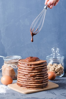 Pfannkuchen-kuchen. ein stapel schokoladenpfannkuchen mit schokoladencreme und -mandeln auf die oberseite.