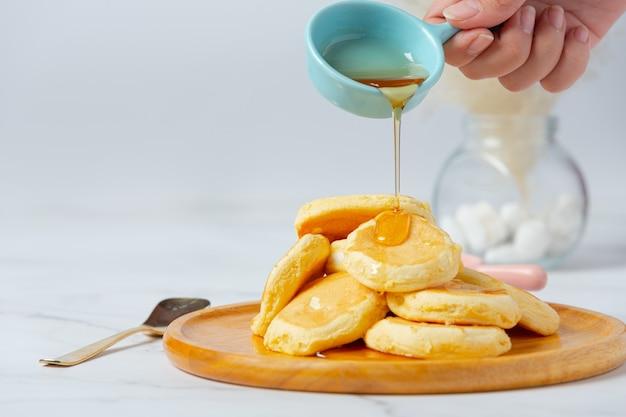 Pfannkuchen mit ahornsirup in platte auf weißem hintergrund