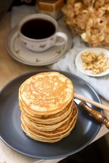 Pfannkuchen mit banane, nüssen und honig, dazu tee. rustikaler stil.