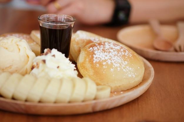 Pfannkuchen mit banane und schokolade auf hölzerner platte, nachtisch