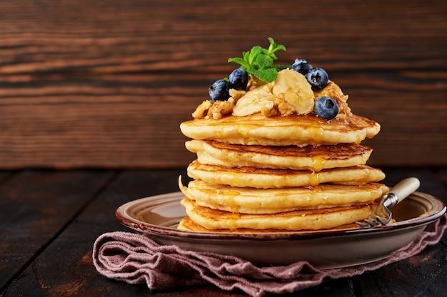 Pfannkuchen mit banane, walnuss, honig und karamell zum frühstück auf dunklem holzhintergrund. selektiver fokus.