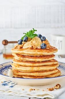 Pfannkuchen mit banane, walnuss, honig und karamell zum frühstück. selektiver fokus.