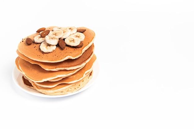 Pfannkuchen mit bananen auf einem teller, auf einer weißen oberfläche, isoliert, mit einem platz für text
