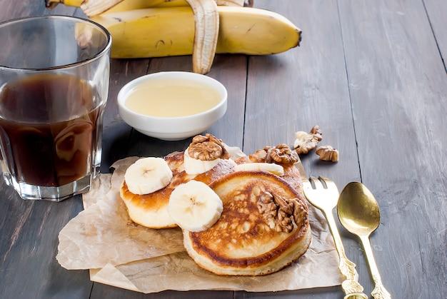 Pfannkuchen mit bananen-, nuss-, honig- und schalenkaffee auf dunkelheit